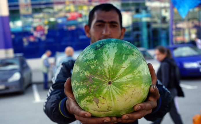 Человек держит арбуз